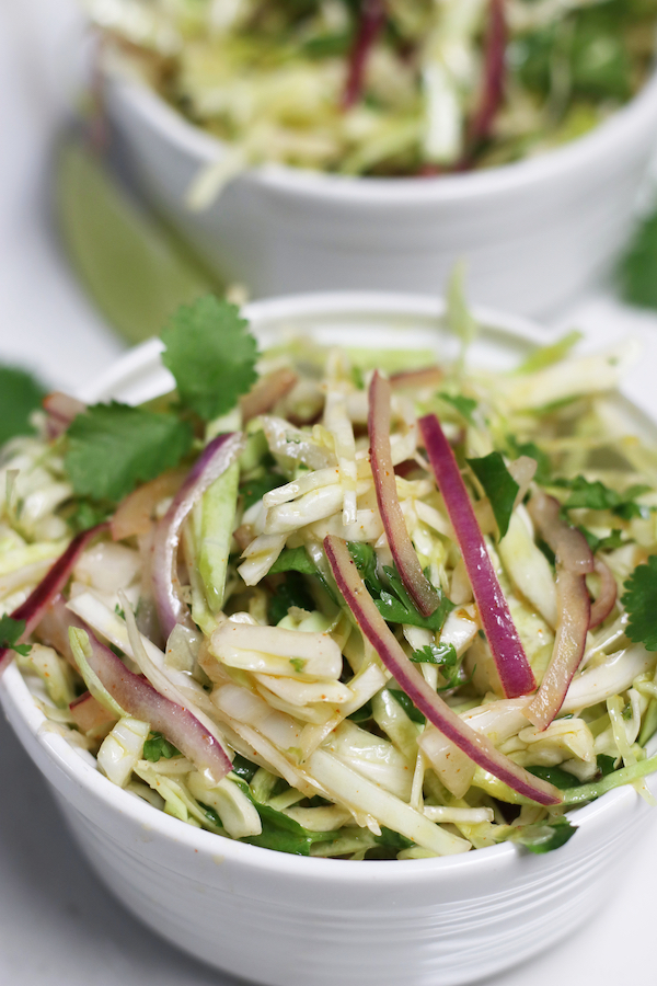 Two single servings of Mexican Cabbage Slaw in small white bowls.