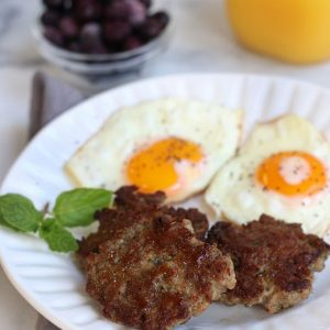 Three Homemade Breakfast Sausages on a white plate with sunny side up eggs.