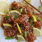 Chinese Lemon Chicken that has been baked and garnished with sesame seeds, lemon slices and green onions.