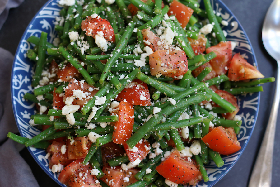 Marinated Green Bean Salad garnished with feta and black pepper.