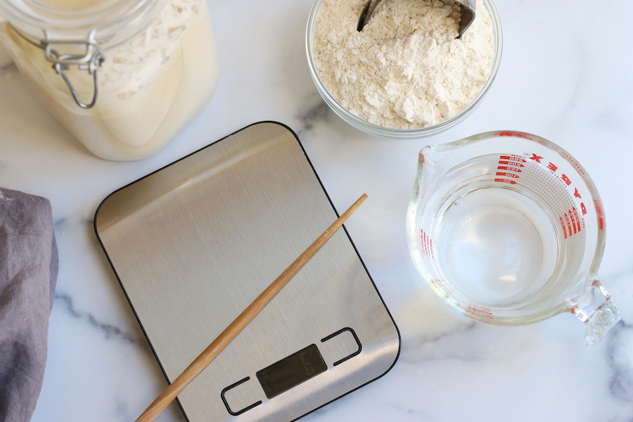 Overhead photo of baking scale, liquid measuring cup, chopstick and glass bowl; tools needed to make sourdough starter.