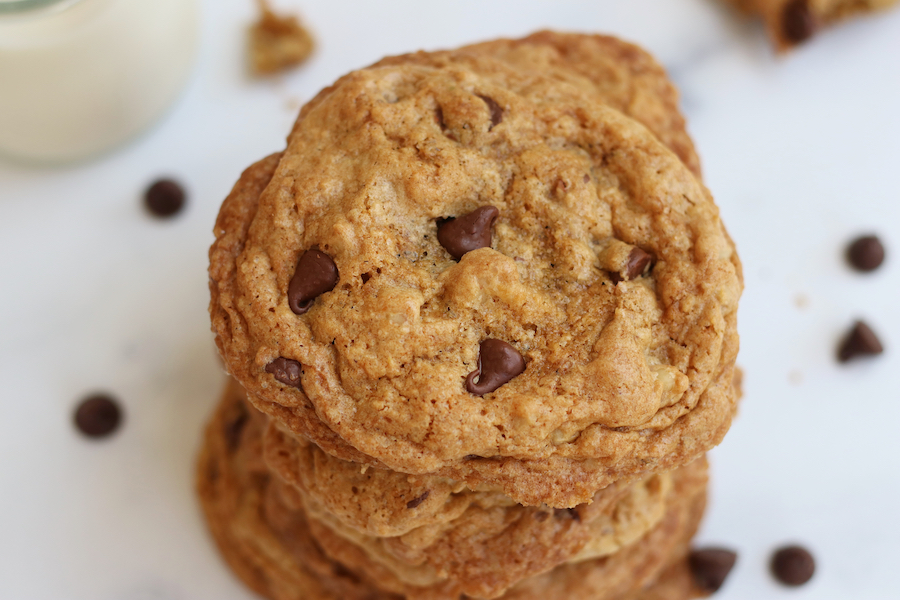 A stack of the Best Vegan Chocolate Chip Cookies sitting on a white counter with chocolate chips.