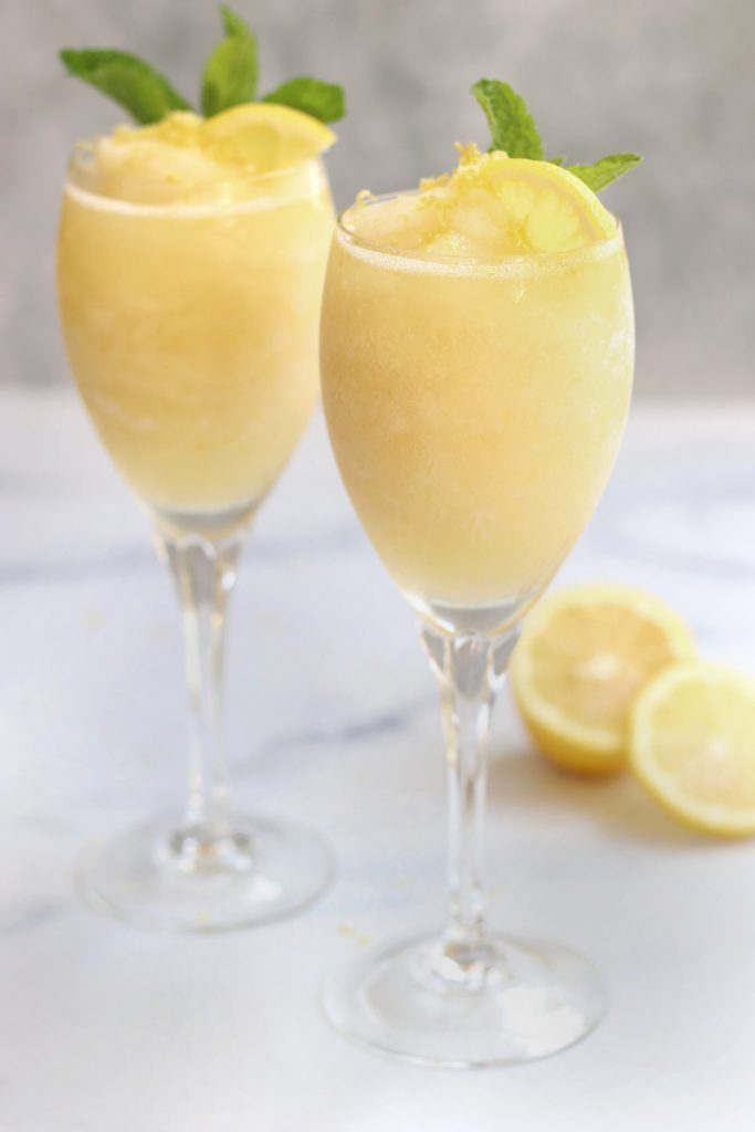 Two crystal glasses of a Lemon Dessert Cocktail sitting on a white countertop.
