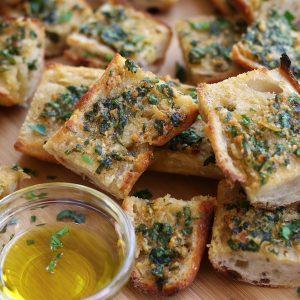 Slices of Garlic Bread From Scratch sitting on a cutting board.
