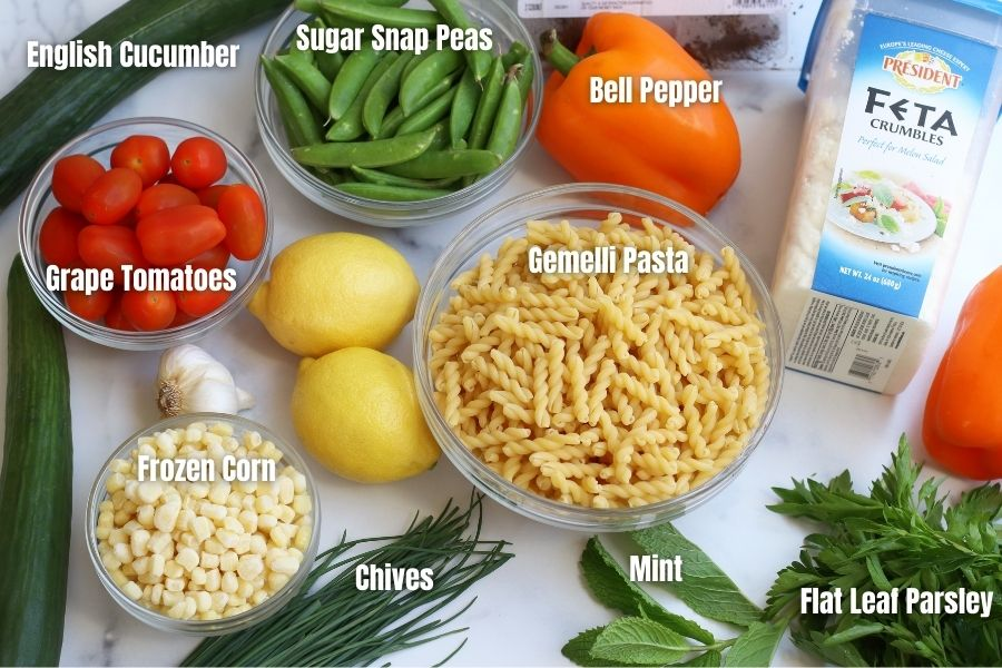 Ingredients for Summer Pasta Salad laid out on a white countertop.