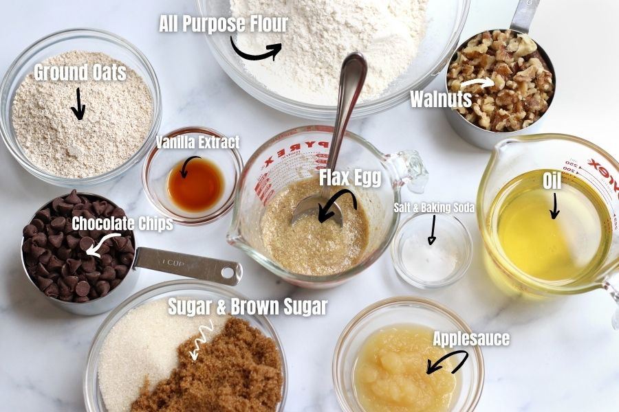 Ingredients for Vegan Chocolate Chip Cookies measured into small bowls laying on a white countertop.