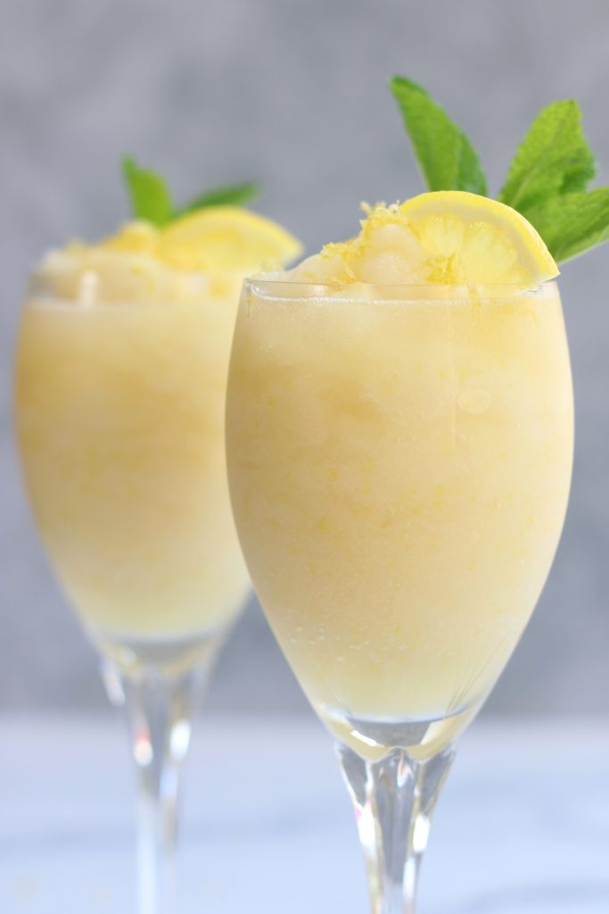Sgroppino al Limone garnished with lemon wedges and fresh mint sprigs.
