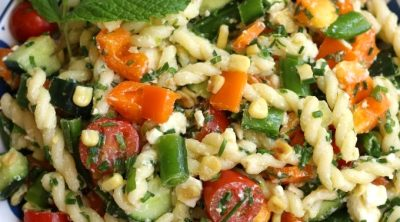 Overhead photo of Summer Pasta Salad with orange bell pepper pieces, fresh mint and chives.