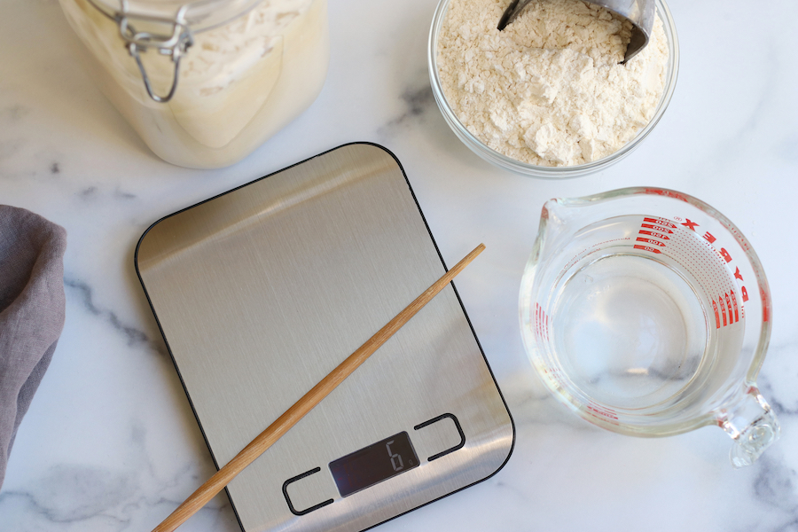 Most of the tools and ingredients needed for Homemade Sourdough Baguettes sitting on a white countertop.