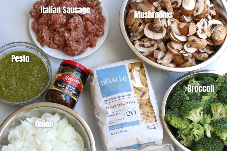 Ingredients for Sausage Pesto Pasta laid out on a white countertop.