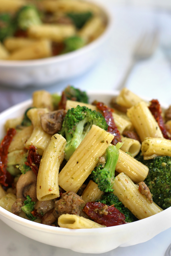 Two bowls of pasta with pesto, sausage, broccoli and sun-dried tomatoes.