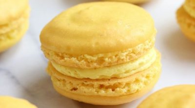 Up close photo of Lemon Macarons on a white countertop.