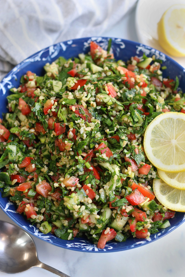 Overhead photo of Tabbouleh in a blue bowl sitting next to a serving spoon.