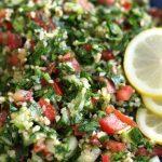 A bowl of Tabouli Salad garnished with fresh lemon slices.