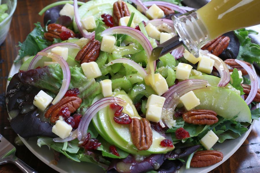 Apple Cider Vinegar Salad Dressing being poured on a green salad with fruit.