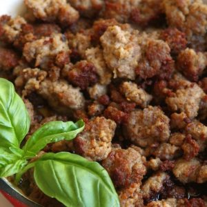 Cooked Homemade Italian Sausage garnished with fresh basil leaves.