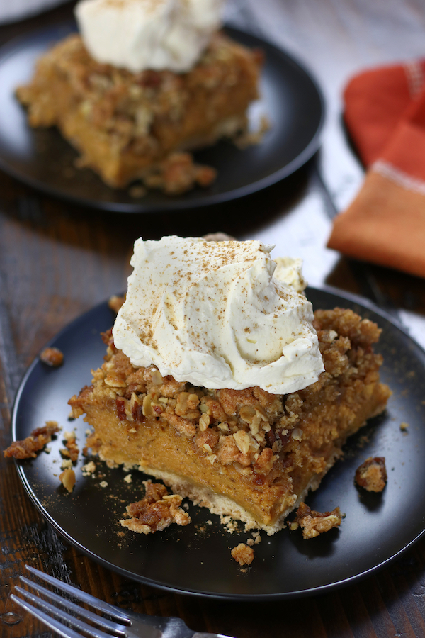 Two servings of Pumpkin Pie Crisp on two black plates.