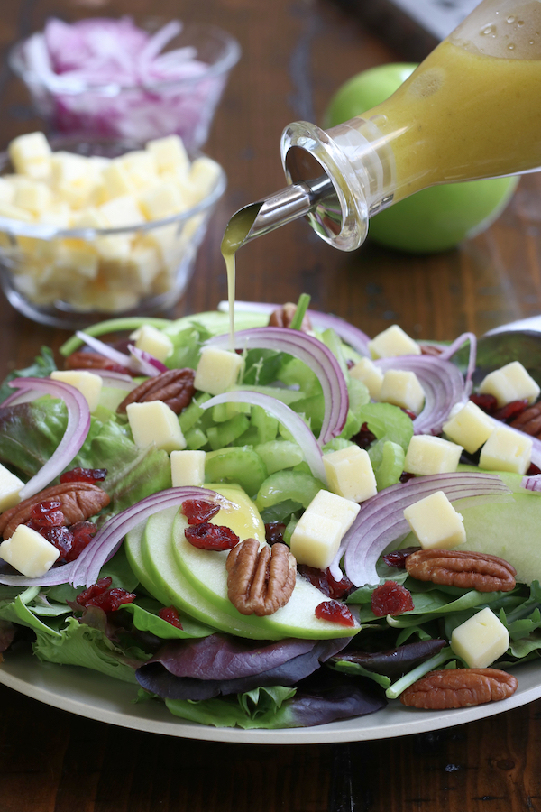 Zesty Apple Cider Vinaigrette being drizzle on a plate of salad.