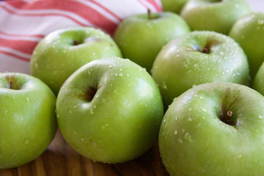 Granny Smith Apples for Apple Crisp sitting on a table with water droplets.
