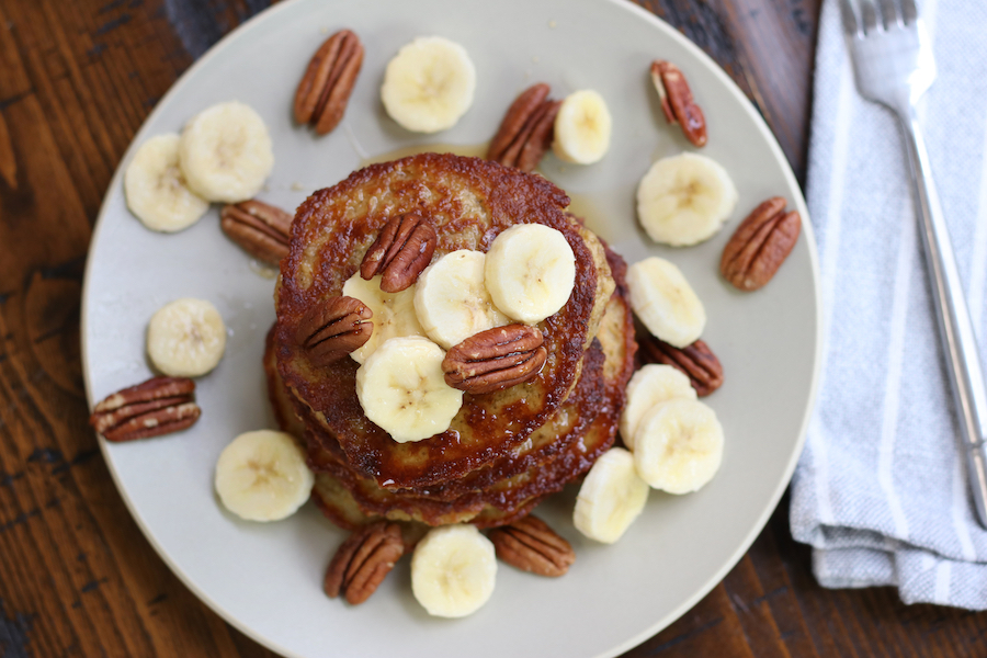 Overhead photo of Banana Oat Pancakes garnished with slices of banana and pecan halves.