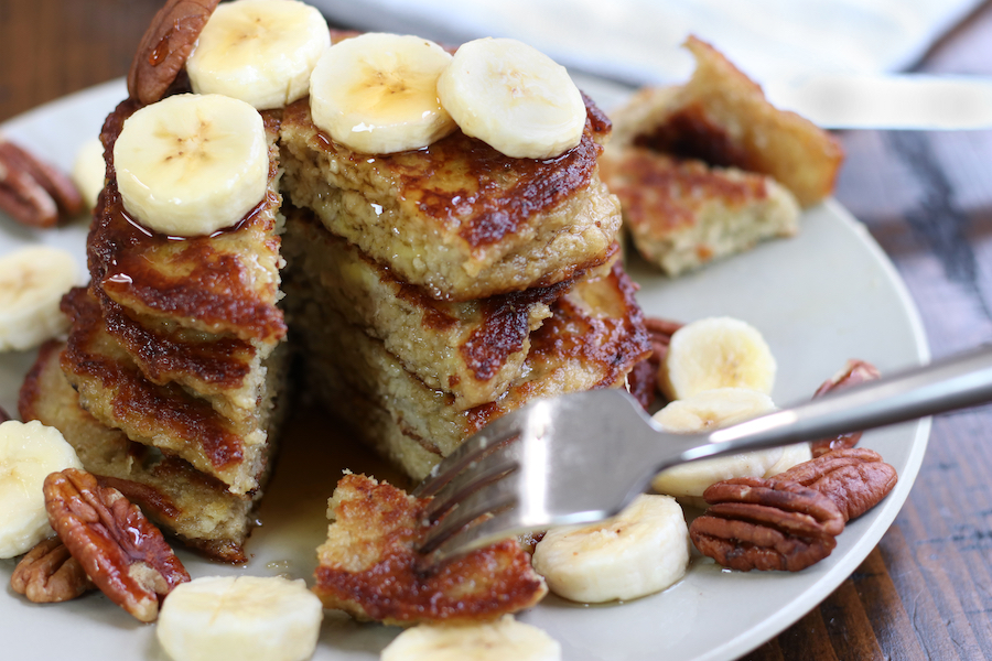 A stack of Healthy Banana Pancakes that have been sliced into.