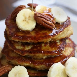 A stack of Oat Banana Pancakes with cut banana slices and pecans.