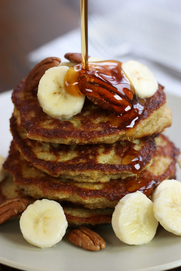 Maple syrup being poured on a stack of Oatmeal Banana Pancakes.